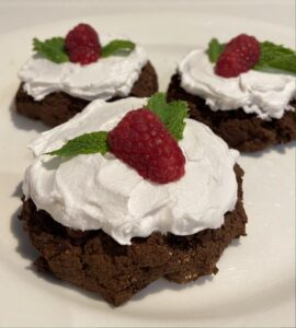 Cocoa whoopie cakes with coconut cream and raspberries
